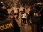 Una pareja escucha las noticias sobre la noche electoral en una calle de Lima, este domingo.