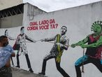 "A man looks to a graffiti with Brazilian President Jair Bolsonaro and a person depicting the coronavirus pulling a rope against health workers in Sao Paulo, Brazil, June 10, 2020. The graffiti reads:""Which side are you?"". REUTERS/Amanda Perobelli"