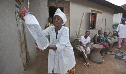 Mulher lava as mãos com água clorada, medida de prevenção contra o ebola, em Serra Leoa.