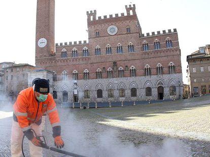 Trabalhador limpa a Piazza del Campo, em Siena, na Itália.