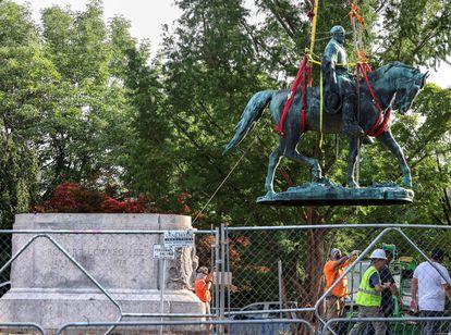 Trabalhadores retiram a estátua de Lee, que ficará guardada até que os vereadores decidam sobre seu futuro.