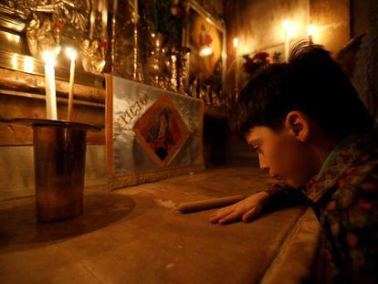 Menino reza na Igreja do Santo Sepulcro, na Cidade Velha de Jerusalém.