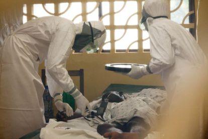 O doutor Brantly (esquerda) trata um paciente de ebola.