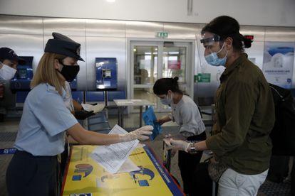 Polícia grega verifica os documentos dos passageiros que chegaram de Doha, no Aeroporto Internacional de Atenas, em 15 de junho.