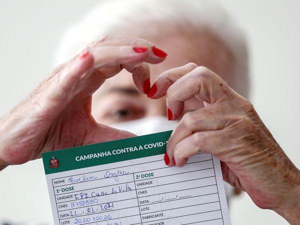 -FOTODELDIA- AME600. SAO PAULO (BRASIL), 21/01/2021.- Una anciana hace la forma de un corazón con sus manos mientras muestra su certificado de vacuna contra la covid-19, durante el proceso de inmunización de adultos mayores hoy, en el instituto de cuidados de larga duración para ancianos del ayuntamiento de la ciudad de Sao Paulo (Brasil). Brasil inició esta semana la inmunización en todo su territorio con tan sólo 6 millones de dosis de la Coronavac, que recibió el visto bueno de la agencia reguladora el pasado domingo, al igual que la fórmula desarrollada por el laboratorio AstraZeneca y la Universidad de Oxford. EFE/ Sebastião Moreira