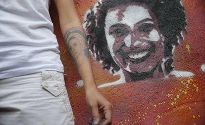 A viúva de Marielle Franco, Mônica Benício, ao lado de grafite da vereadora assassinada.