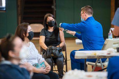 Uma mulher recebe sua segunda dose da vacina Moderna na clínica ambulante de vacinação contra covid-19 em Connecticut.