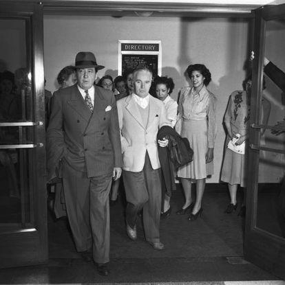 """Em 1943, o célebre comediante Charles Chaplin se viu envolvido em uma bela confusão quando a atriz Joan Barry anunciou em alta voz que estava grávida dele. Após um ruidoso julgamento, Chaplin precisou assumir a criança. Além disso, foi acusado de levar Joan de Los Angeles a Nova York em uma viagem de amantes, quebrando a Lei Mann, delito federal que proibia o transporte de mulheres através dos limites interestaduais """"com propósitos imorais"""". Agora é muito mais comum, mas nos anos 40 era um escândalo cinquentões se relacionarem com jovens de vinte anos. Chaplin quase sempre se relacionava com menores de 20: em 1944, quando tinha 54 anos, se casou com Oona O'Neill, de 18 anos, com quem teria oito filhos. Na imagem, Charlie Chaplin, acompanhado por seu advogado, Jerry Giesler, após o julgamento pelo filho que teve com Joan Barry."""