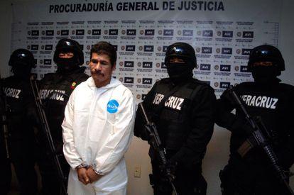"""Pessoal da Procuradoria Geral de Justiça do Estado escolta José Antonio Hernández, conhecido como """"El Silva"""", quando foi apresentado como responsável pelo homicídio."""