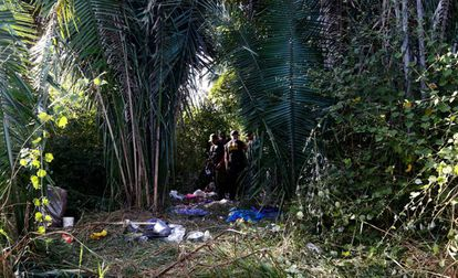 Nesta quinta-feira, policiais examinam a fazenda onde dez posseiros foram mortos.