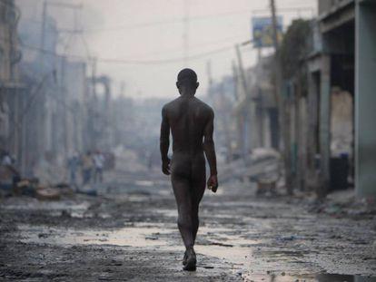 Um homem nu caminha pelas ruas destruídas de Porto Príncipe após o grande terremoto de 12 de janeiro de 2010.