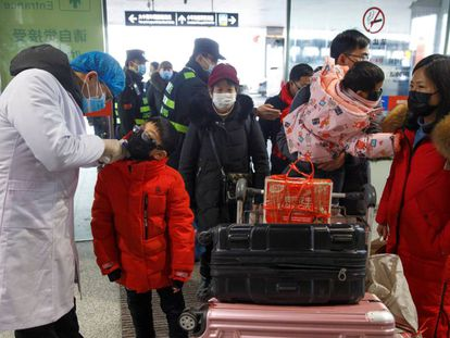 Médico mede a temperatura de passageiros antes do embarque no aeroporto de Changsha, na China.
