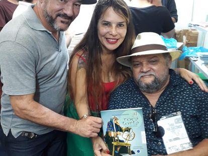 Cláudio Cardoso, sentado à direita, ao lado de Sol de Souza e de outro amigo. Cláudio, de 58 anos, foi uma das 100.000 vítimas fatais da covid-19 no Brasil.
