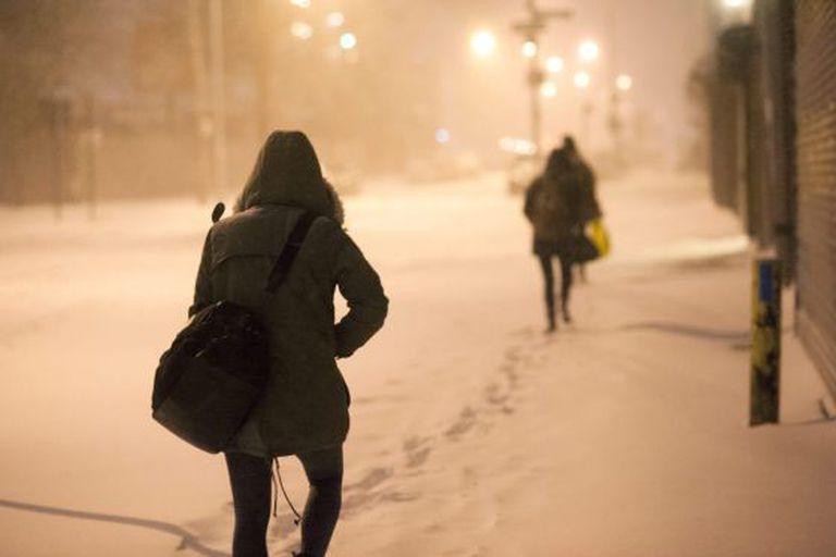 Pedestres caminham por uma rua nevada em Nova York.