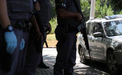 Policiais da Rota diante do carro alvejado por tiros em Guararema (SP).