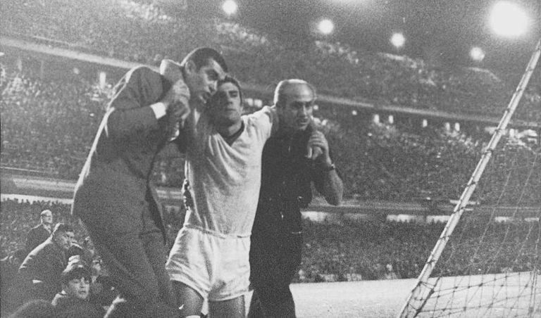 Combin, do Milan, deixa o campo com o rosto ensanguentado.