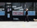 A woman takes walk with a dog in front of the closing signs displayed in a store's window front in Niles, Ill., Wednesday, May 13, 2020. (AP Photo/Nam Y. Huh)