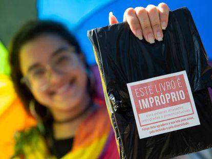 Mulher exibe livro distribuído de graça em ação de Felipe Neto na Bienal do Rio.