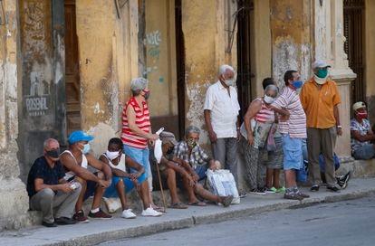 Várias pessoas esperam sua vez para comprar alimentos na sexta-feira em Havana.