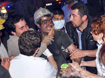 Um mineiro resgatado é abraçado por seus colegas.