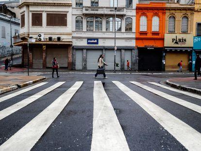 Pessoas caminham na rua 25 de Março no primeiro dia da fase vermelha em São Paulo.