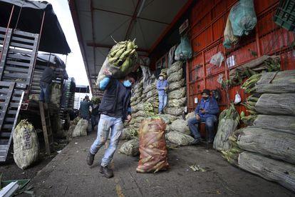 Um homem de máscara carrega um saco de milho em Corabastos, um dos maiores centros de distribuição de alimentos da América Latina, em Bogotá (Colômbia), na terça-feira da semana passada.