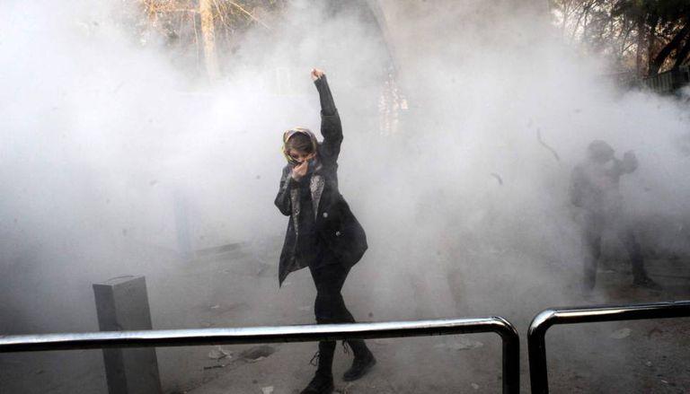 Uma jovem ergue o punho durante os choques entre manifestantes e polícia na Universidade de Teerã.