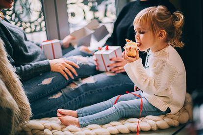 Menina come doce depois de ganhar os presentes de Natal.