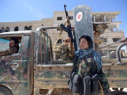 Um Alí posa com sua arma no centro do vilarejo sírio Al Qariatein depois de combater e expulsar o EI da localidade.