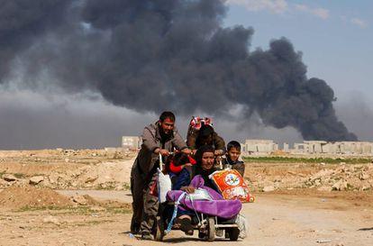 Desalojados iraquianos deixam suas casas por causa dos confrontos entre o Exército iraquiano e o Estado Islâmico em Mossul.