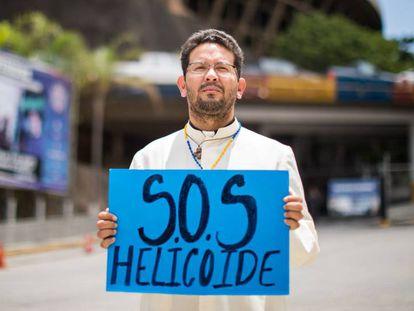 Um sacerdote sustenta um cartaz em frente à sede do Serviço de Inteligência, em Caracas.