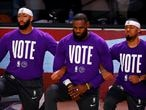 LAKE BUENA VISTA, FLORIDA - SEPTEMBER 22: Anthony Davis #3 of the Los Angeles Lakers, LeBron James #23 of the Los Angeles Lakers and Quinn Cook #28 of the Los Angeles Lakers kneel during the National Anthem with VOTE shirts on prior to the start of the game against the Denver Nuggets in Game Three of the Western Conference Finals during the 2020 NBA Playoffs at AdventHealth Arena at the ESPN Wide World Of Sports Complex on September 22, 2020 in Lake Buena Vista, Florida. NOTE TO USER: User expressly acknowledges and agrees that, by downloading and or using this photograph, User is consenting to the terms and conditions of the Getty Images License Agreement. (Photo by Mike Ehrmann/Getty Images)
