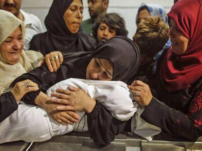 Mulher palestina abraça nesta terça sua filha de oito meses, morta nos confrontos com Israel na Faixa de Gaza.
