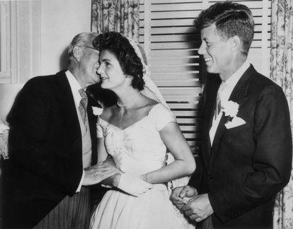Joseph Kennedy (1888-1969) sussurra algo no ouvido de sua nova nora, Jacqueline Bouvier, no dia do casamento, enquanto o marido, John F. Kennedy, observa, sorridente. Foi em Newport, Rhode Island, em 12 de setembro de 1953.