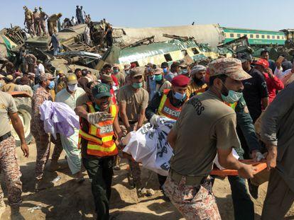 Membros das equipes de resgates sobre o teto de um dos vagões acidentados no choque entre dois trens na província paquistanesa de Sindh, nesta segunda-feira.