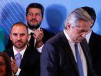 El ministro de Economía de Argentina, Martín Guzmán (de corbata celeste) mira al presidente, Alberto Fernández (el único de pie).