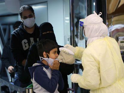 Funcionário de aeroporto na Arábia Saudita mede a temperatura de uma criança vinda da China, onde começou a circular o coronavírus.