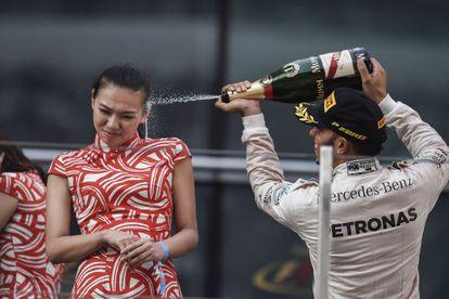 Lewis Hamilton comemora sua vitória em Xangai jogando champanhe em uma assistente chinesa.