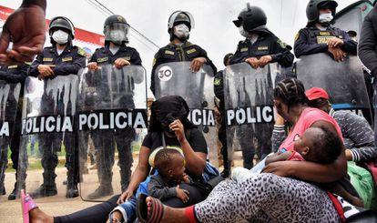 Duas mães migrantes diante do bloqueio policial na cidade peruana de Iñapari, na fronteira com o Brasil, na quinta-feira.