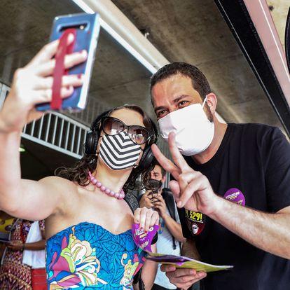 AME8816. SAO PAULO (BRASIL), 02/10/2020.- Guilherme Boulos, candidato a la Alcaldía de Sao Paulo por el Partido Socialismo y Libertad (PSOL), se toma hoy una foto con una simpatizante durante un acto de campaña en la estación de metro Anhangabaú, en el centro de Sao Paulo (Brasil). Más de 148 millones de personas están habilitadas para votar en los comicios municipales del próximo 15 de noviembre en Brasil. EFE/ Sebastiao Moreira