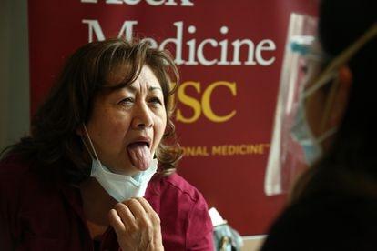 Uma mulher mostra a língua para uma enfermeira em Los Angeles, na Califórnia, em 23 de janeiro de 2021