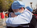 A medical worker (R) embraces a member of a medical assistance team from Jiangsu province at a ceremony marking their departure after helping with the COVID-19 coronavirus recovery effort, in Wuhan, in China's central Hubei province on March 19, 2020. - Medical teams from across China began leaving Wuhan this week after the number of new coronavirus infections dropped. China on March 19 reported no new domestic cases of the coronavirus for the first time since it started recording them in January, but recorded a spike in infections from abroad. (Photo by STR / AFP) / China OUT