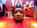 """La cabeza gigante de la foto es una de las esculturas de la exposición 'Segredos' (Secretos), del dúo brasileño OsGemeos, uno de los máximos exponentes del arte urbano internacional. Inaugurada el pasado 15 de octubre en la Pinacoteca de São Paulo (<a href=""""http://pinacoteca.org.br/"""" target=""""_blank"""">pinacoteca.org.br</a>), marca el renacimiento cultural de la ciudad brasileña tras el parón por la pandemia con un viaje al universo """"onírico, lúdico y pulsante"""" de los gemelos Otávio y Gustavo Pandolfo (São Paulo, 1974), dos artistas conocidos por sus vistosos murales y esculturas en metrópolis de todo el mundo y sus característicos personajes amarillos. Influenciados por la cultura 'hip hop', los hermanos se iniciaron en el arte urbano en 1987 en las paredes del barrio paulista de Cambuci; hoy sus trabajos se exhiben y subastan en museos y galerías de arte, y también han decorado aviones y trenes. Además de grafitis, esculturas, dibujos y cuadros, 'Secretos' reúne hasta el 22 de febrero de 2021 cerca de un millar de objetos personales, herramientas, cuadernos y bocetos que nunca habían sido mostrados al público."""