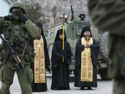 Sacerdotes ortodoxos rezam perto de soldados russos na Balaclava (Crimeia).