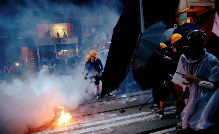 Manifestantes se protegem de gases lacrimogêneos.