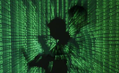Homem segura uma laptop com um fundo binário.