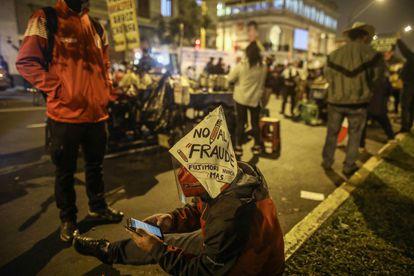Simpatizantes de Pedro Castillo esperam os resultados eleitorais na noite de quarta-feira, em frente à sede de sua campanha em Lima (Peru).