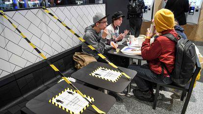 Jovens em lanchonete com capacidade reduzida, em Estocolmo, na semana passada.