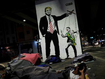 Sem-teto diante de grafite que ironiza a relação de Trump e Bolsonaro.