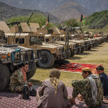 Afghan armed men supporting the Afghan security forces against the Taliban stand with their weapons and Humvee vehicles at Parakh area in Bazarak, Panjshir province on August 19, 2021. (Photo by Ahmad SAHEL ARMAN / AFP)